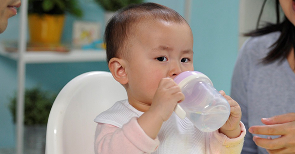 Help babies drink from a cup.